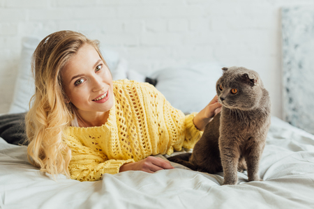 beautiful girl in knitted sweater looking at camera and stroking scottish fold cat while lying in bed at home