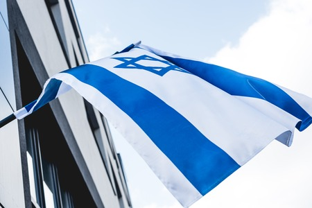 low angle view of israel flag with star of david near building against sky