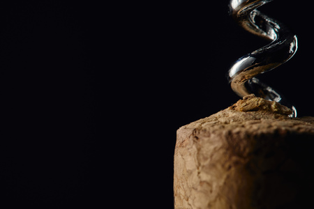 Close up view of wooden cork and corkscrew isolated on black