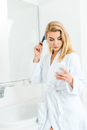 beautiful and blonde woman holding comb and using smartphone in bathroom