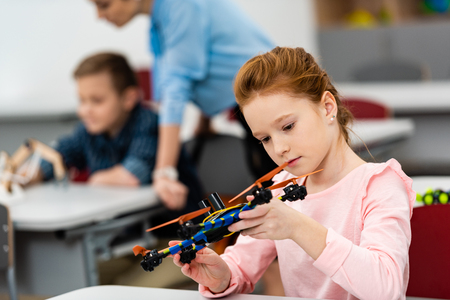 Ginger schoolgirl playing with educational toy during lesson in classroom