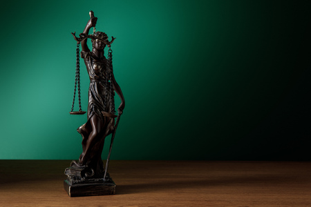 bronze statuette with scales of justice on wooden surface on dark green background