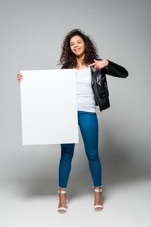 beautiful curly african american girl pointing with finger at blank placard while standing on grey