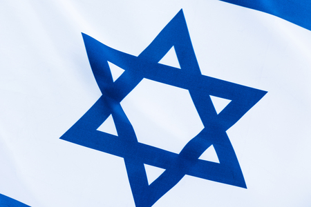 close up of blue star of david on flag of israel