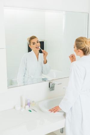 beautiful woman in white bathrobe brushing teeth and looking at mirror