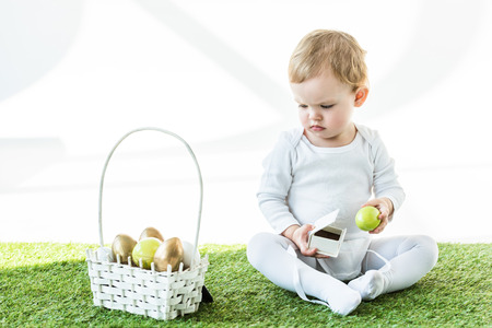 cute kid holding white box and yellow chicken egg while sitting near straw basket with Easter eggs isolated on white