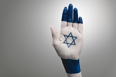cropped view of female hand with blue star of david on grey