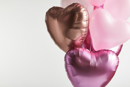 bundle of heart-shaped pink and golden balloons isolated on white with copy space