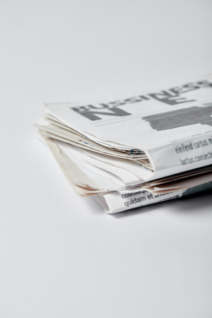 selective focus of business newspapers with lettering on white