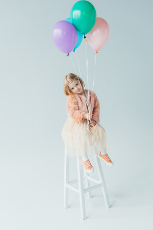 cute kid in faux fur coat and skirt sitting on highchair, looking at camera and holding balloons