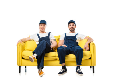 two smiling movers in uniform sitting on yellow sofa and looking at camera isolated on white
