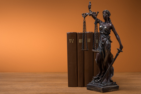 bronze statuette with scales of justice and row of brown books on table