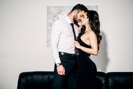 hermosa chica en vestido negro besando a un hombre guapo en traje Foto de archivo