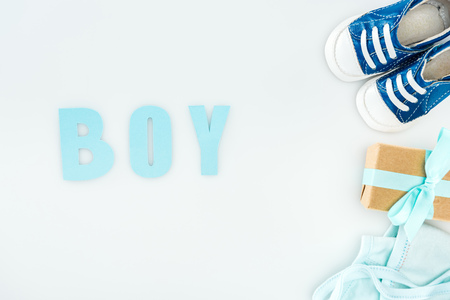 top view of blue sneakers, gift box and bonnet, boy lettering on white background with copy space 스톡 콘텐츠