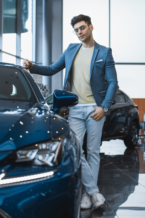 selective focus of man in glasses standing near automobile with crossed legs in car showroom