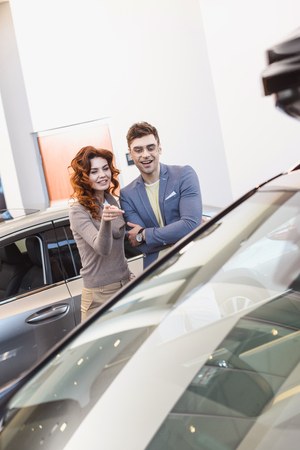 selective focus of cheerful curly woman pointing with finger at car near handsome man Stock Photo