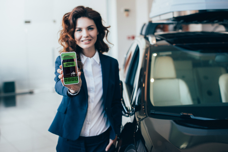 selective focus of  smiling businesswoman holding smartphone with booking app on screen and holding hand in pocket Stock Photo