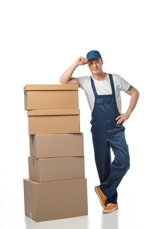 handsome mover in uniform with cardboard boxes looking at camera while adjusting hat isolated on white