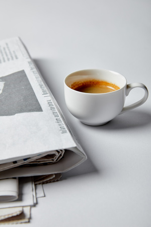 selective focus of cup of coffee near newspapers on white