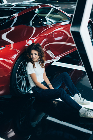 selective focus of happy woman sitting on floor near new red car Stok Fotoğraf