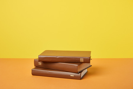 Brown books on bright orange surface isolated on yellow