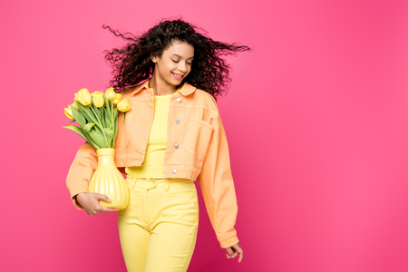 cheerful african american girl holding vase with yellow tulips while standing isolated on crimson 版權商用圖片