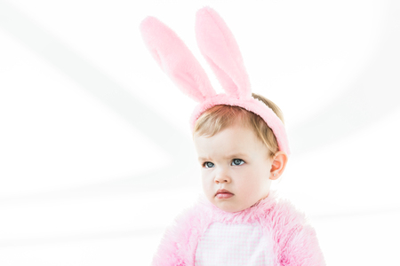 adorable pensive baby in bunny ears headband looking away isolated on white