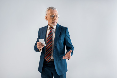 mature businessman in suit holding smartphone and gesturing isolated on grey Stockfoto
