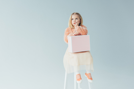thoughtful kid in faux fur coat and skirt sitting on highchair and holding pink case isolated on grey Stock Photo