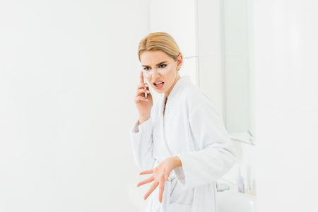 beautiful and irritated woman in white bathrobe with eye patches on face talking on smartphone
