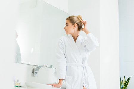 attractive and blonde woman in white bathrobe looking at mirror in bathroom