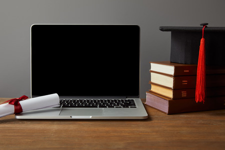 Laptop with blank screen, books, diploma and academic cap on wooden table isolated on grey Stockfoto