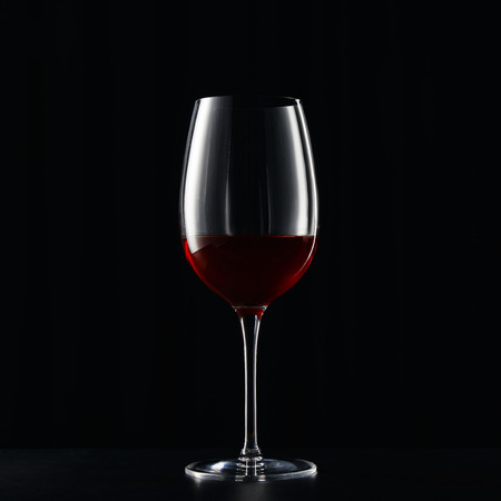 Glass of red wine on dark surface isolated on black