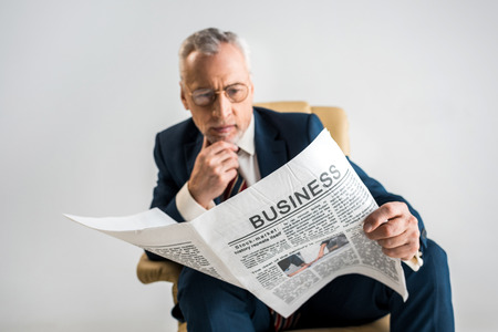 selective focus of mature businessman in glasses reading business newspaper isolated on grey