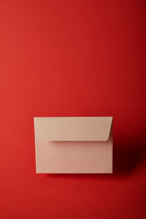 beige, blank and empty envelope on bright colorful red background with copy space 스톡 콘텐츠