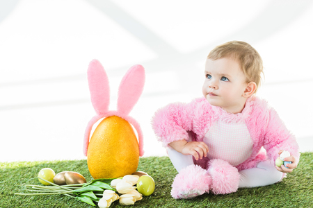 adorable child in pink fluffy costume sitting near yellow ostrich egg with bunny ears headband, colorful Easter eggs and tulips isolated on white