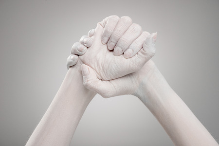 cropped view of female hands painted in white with clenched hands on grey Banco de Imagens