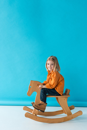 blonde and cute kid sitting on rocking horse and looking at camera on blue background