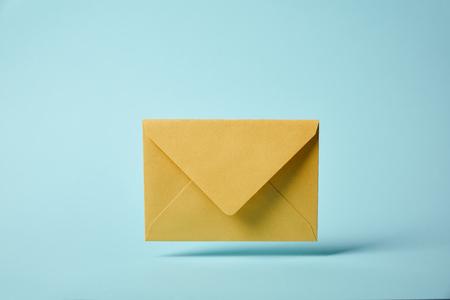 gele en kleurrijke envelop op blauwe achtergrond met kopie ruimte Stockfoto