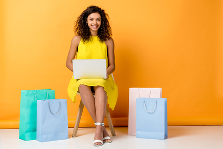 attractive curly african american girl sitting in yellow dress on chair and using laptop near shopping bags on orange