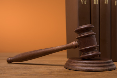 close up of volumes of brown books in leather covers and gavel on wooden table isolated on orange Imagens