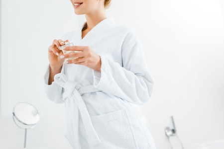 cropped view of woman in white bathrobe holding perfume in bathroom