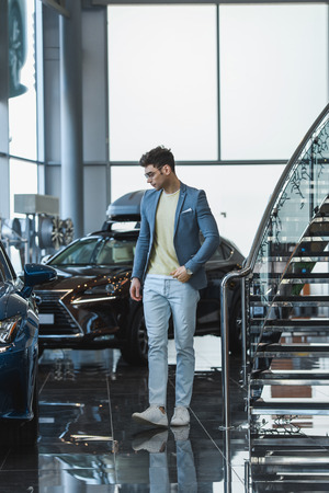 stylish man in glasses standing near automobiles in car showroom