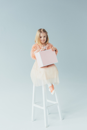 kid in faux fur coat and skirt sitting on highchair and holding pink case on grey background