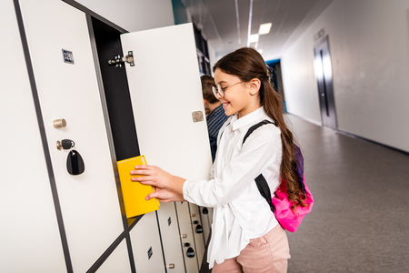 Joyful schoolgirl in glasses putting book in locker during brake in school Banco de Imagens