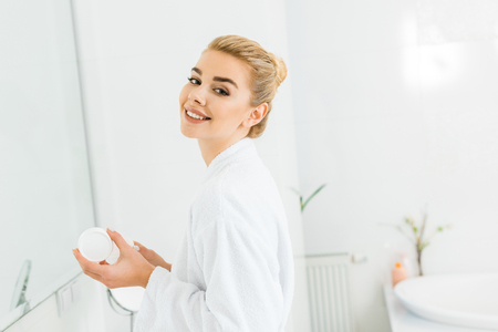 smiling woman in white bathrobe holding cosmetic cream and looking at camera in bathroom Archivio Fotografico