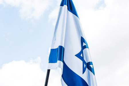 low angle view of national flag of israel with blue star of david against sky with clouds Stock Photo