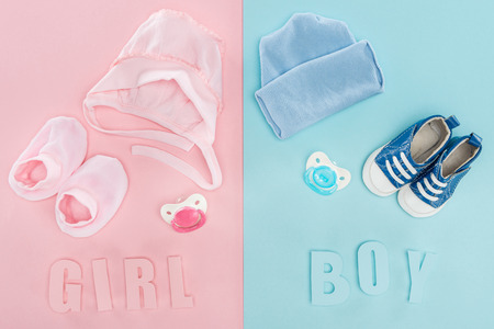 top view of pacifiers, hat, bonnet, booties,sneakers and boy, girl lettering 스톡 콘텐츠