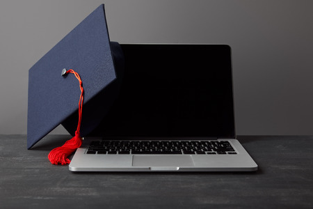 Laptop with blank screen and academic cap with red tassel on grey