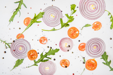 background with sliced tomatoes, red onions, arugula leaves and spices Imagens